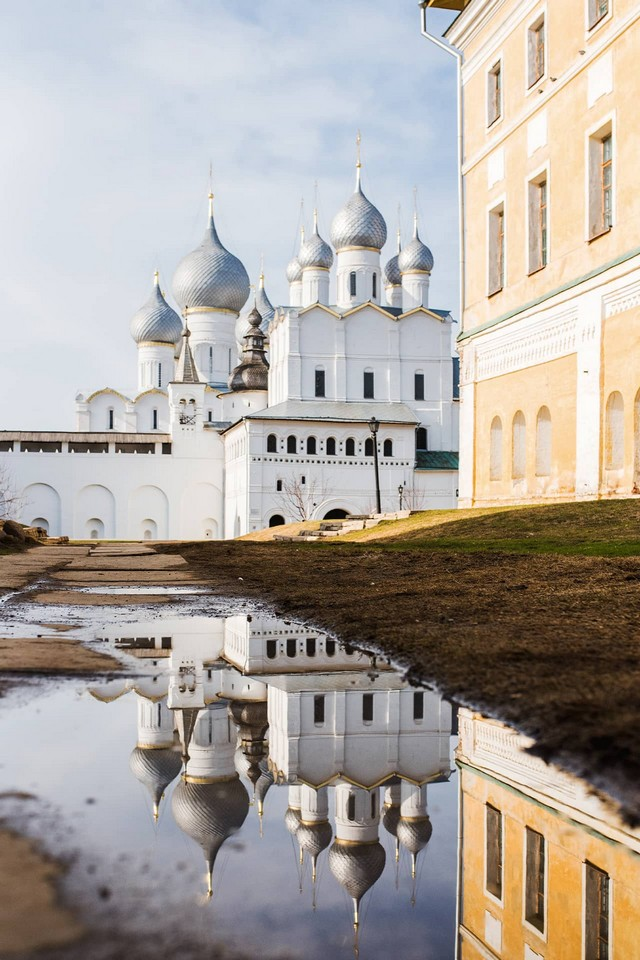 A white cathedral with silver domes, its reflection in the puddle of water