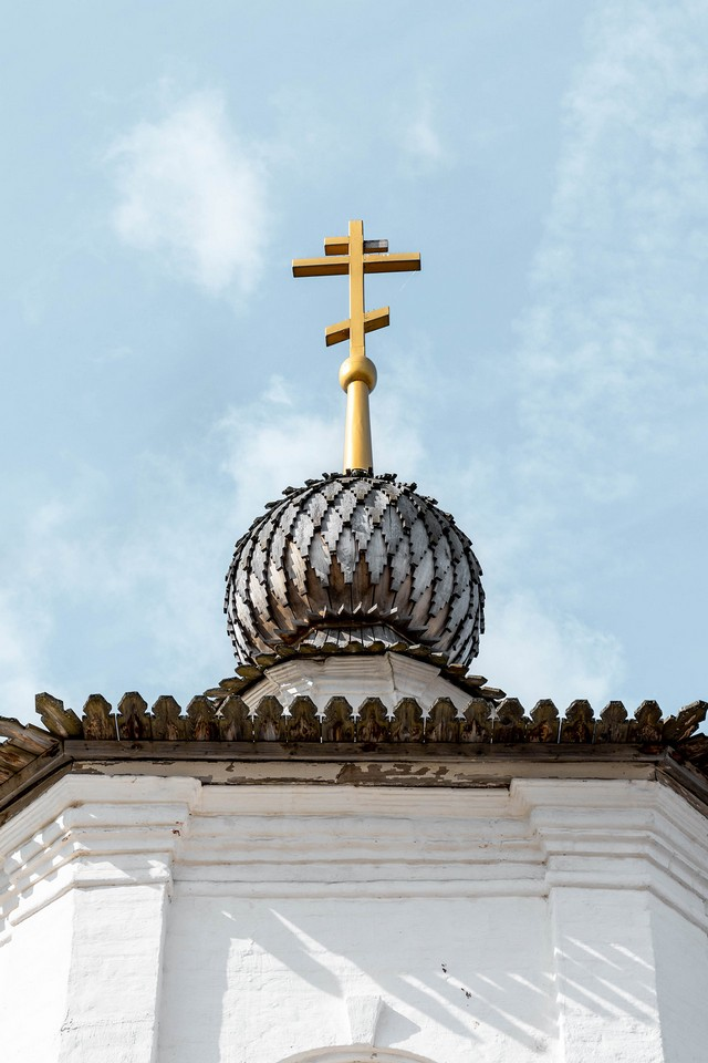 A top of a cathedral with a silver dome and an orthodox cross on the top of it