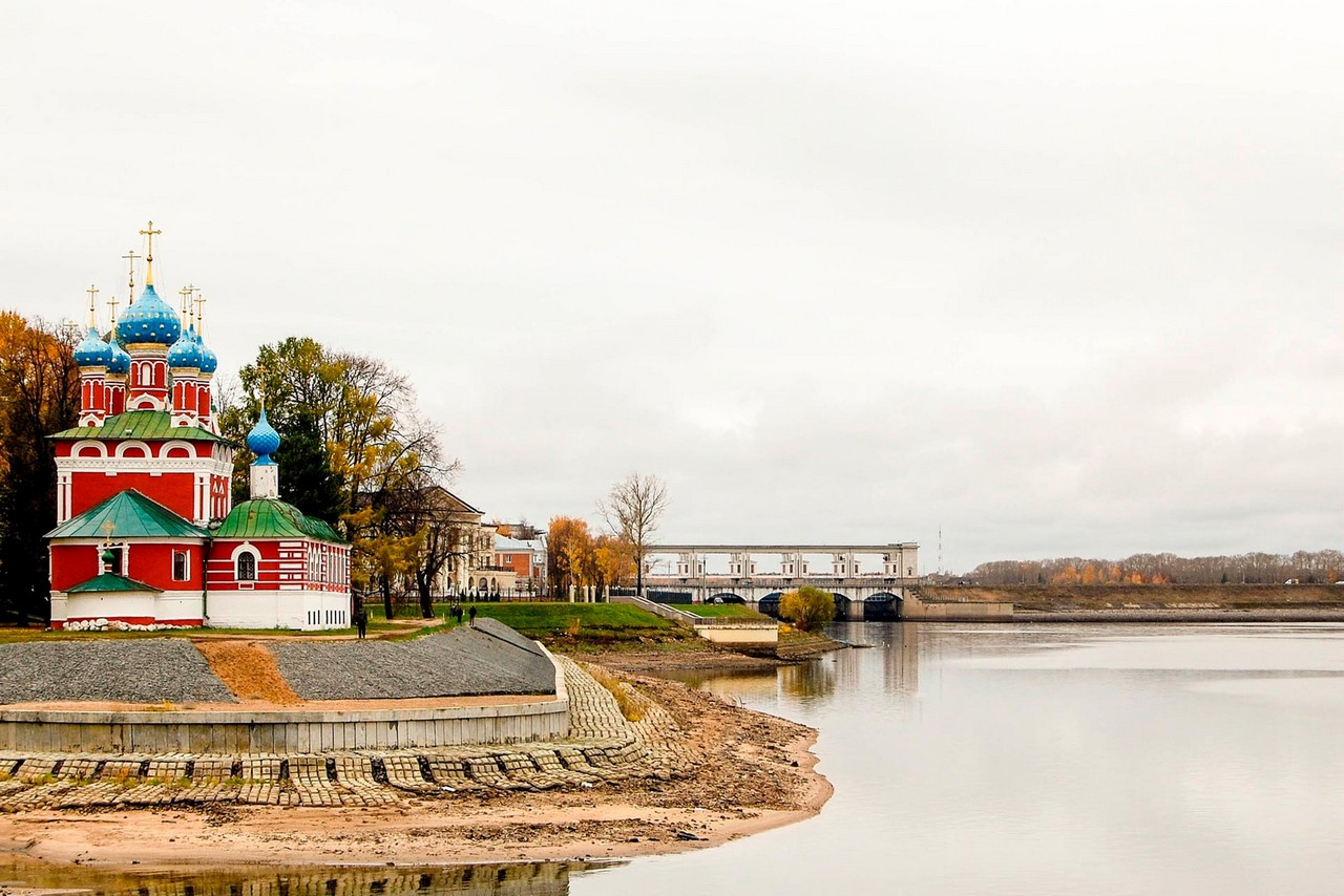 A wide river and a red church in distance, a bridge far off