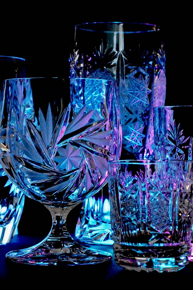 Glasses made of natural crystal shining in darkness