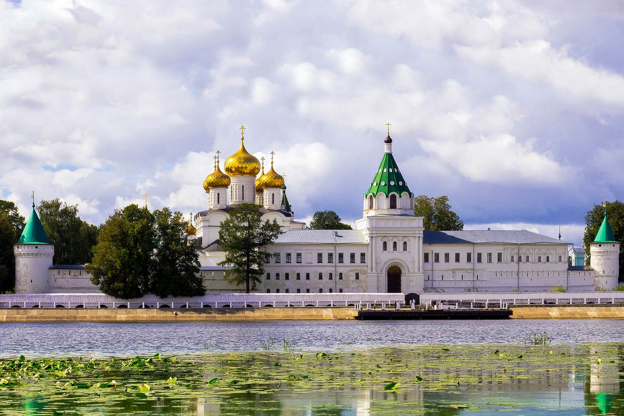 View of a monastery on the bank of a river. Architectural ensemble of Orthodox churches and buildings surrounded with white wall, tower with green roof and gilded onion domes of a church behind the wall