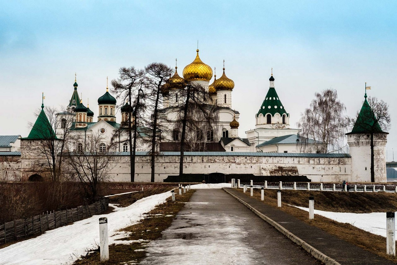 A road to a monastery in winter. A symmetric Orthodox church with gilded onion domes behind the wall, green-roofed towers.