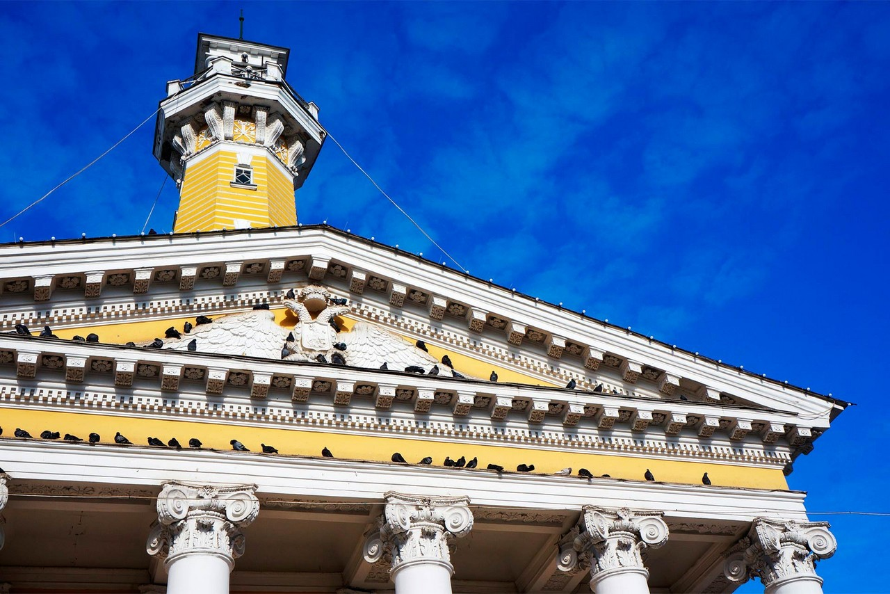 A yellow classical building topped with a tower, portico with Greek columns, a two-headed eagle at the building gable