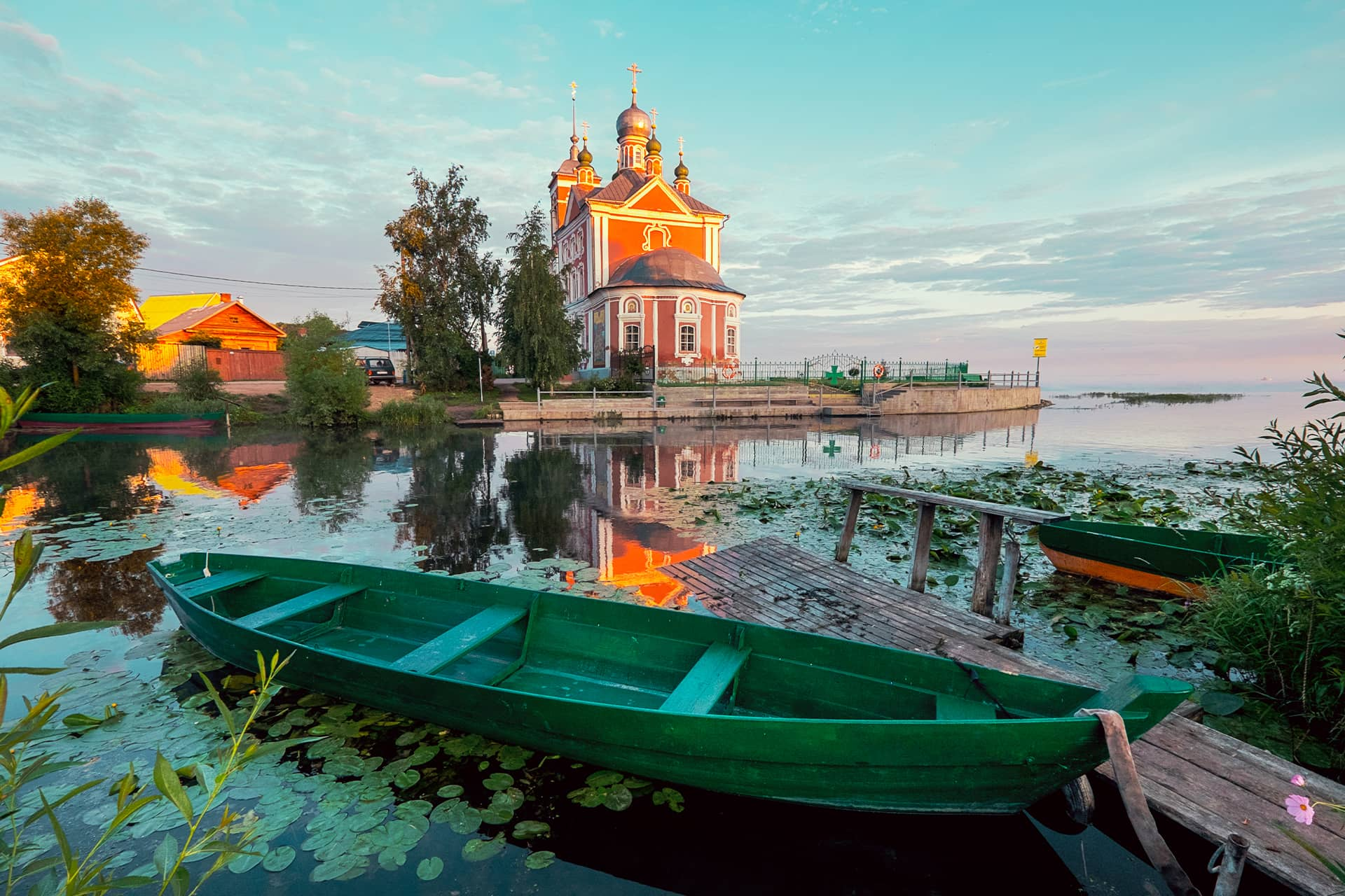 A picturesque small red church on the lake, green metal fence with a cross, a wooden fishing boat on the lake