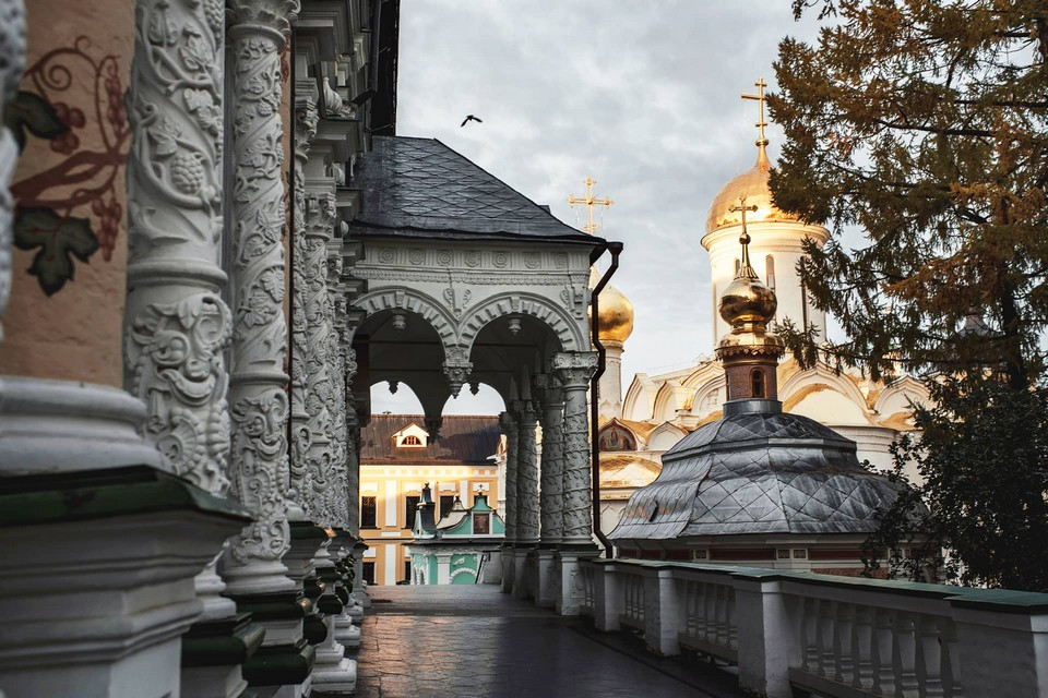 White carved portico and columns of a church in Russian style. Columns decorated with grape-vine. Gilded domes in the background