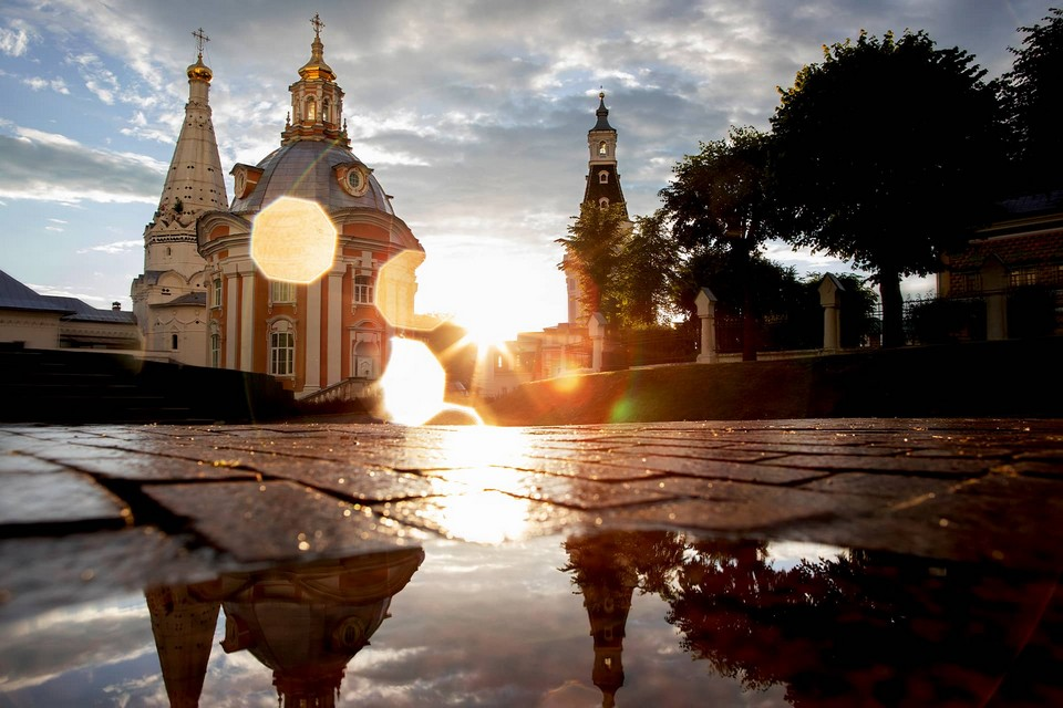 Bright sun after the rain, small red and white church in front of a white tower and it's reflection if a puddle of water