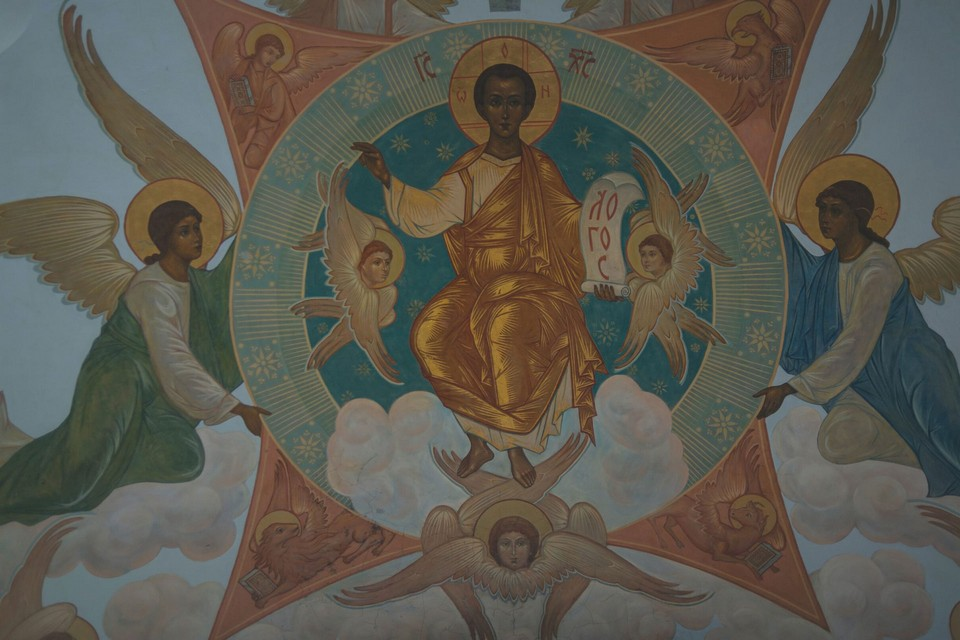 The Holy image of a saint with golden nimbus and golden clothes surrounded by angels. A fresco on the ceiling of an Orthodox church