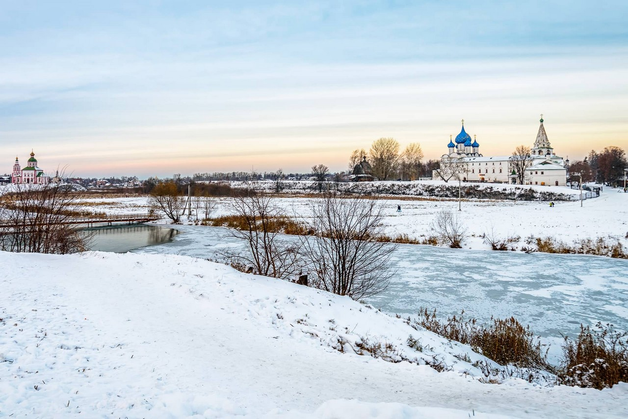 Frozen river in winter, Kremlin and white cathedral with star-studded blue domes on the other side of the river