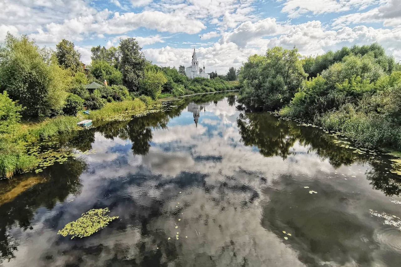 A river with the reflection of the sky and clouds in it, green trees on the banks, white orthodox church from afar.