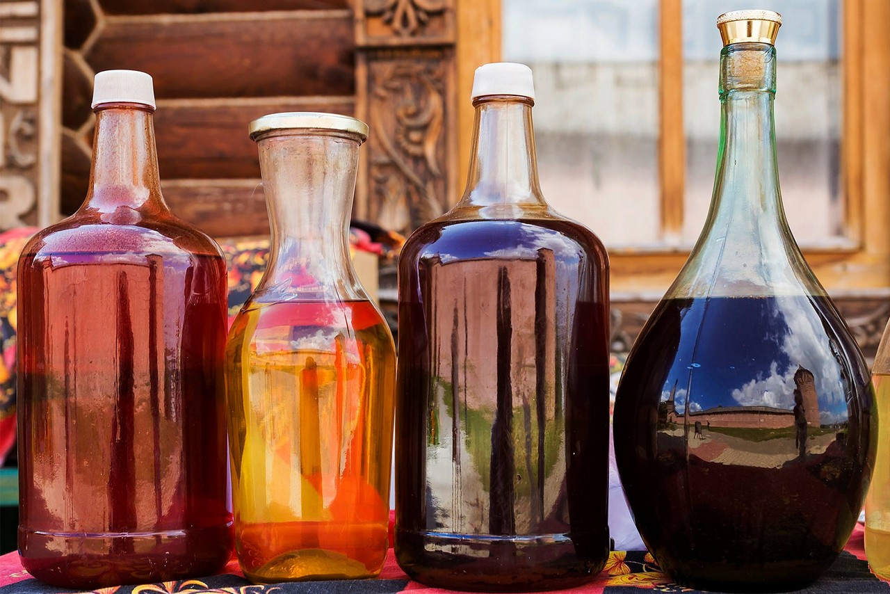 Four glass bottles of different shapes with honey wine