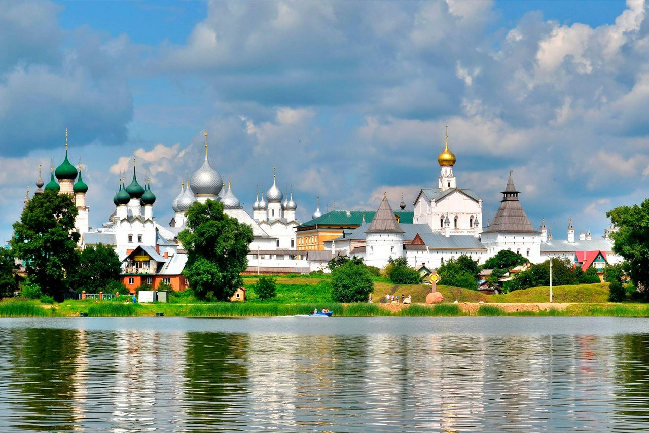 View of a monastery on the bank of a lake. Architectural ensemble of Orthodox churches with green, gilded and green domes