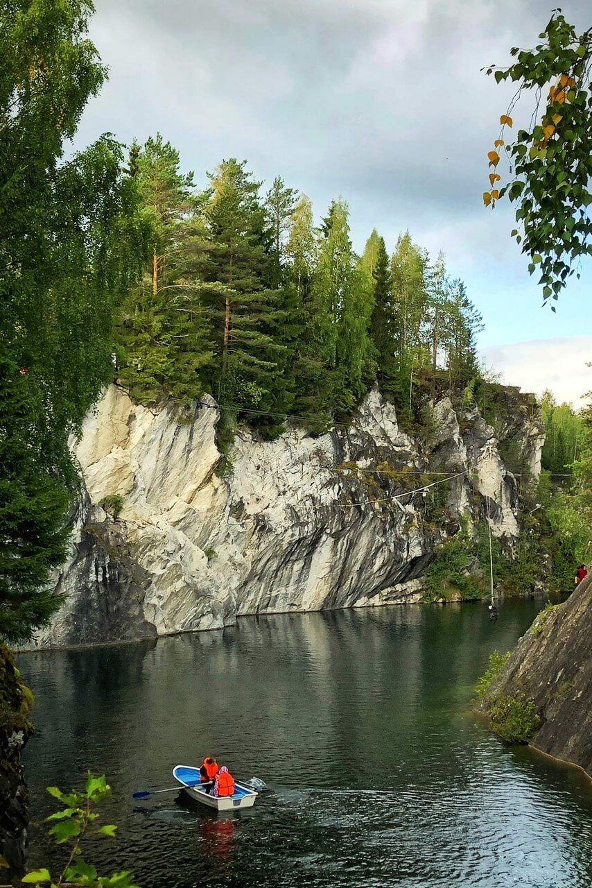 Sharp marble cliffs covered with forest, marble quarry with crystal clean water, a row boat on the water with two men wearing orange life vests