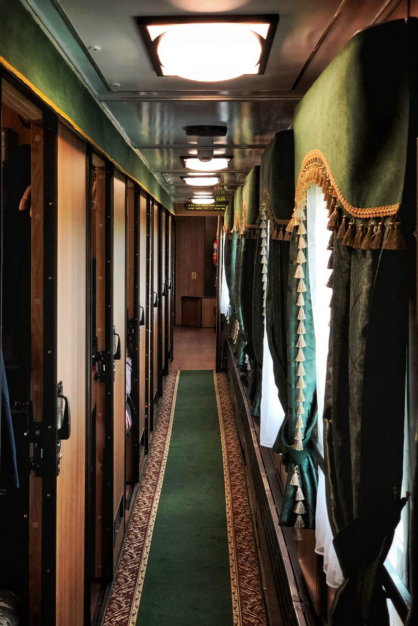 The interior of a vintage steam train of the 20th century. An aisle with green floor covering, windows with green vintage curtains