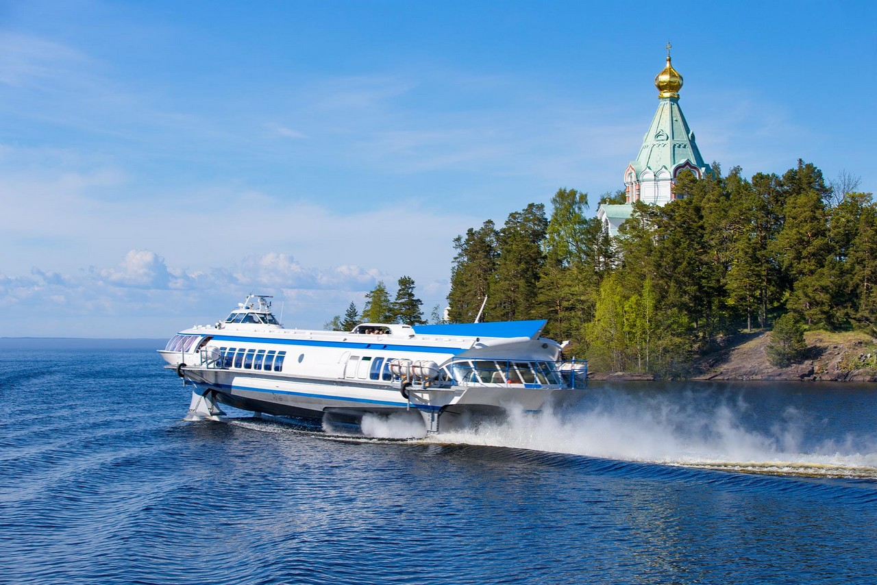 A hydrofoil passenger boat on the lake, island with cliffs, green trees and a church on it, northern nature.