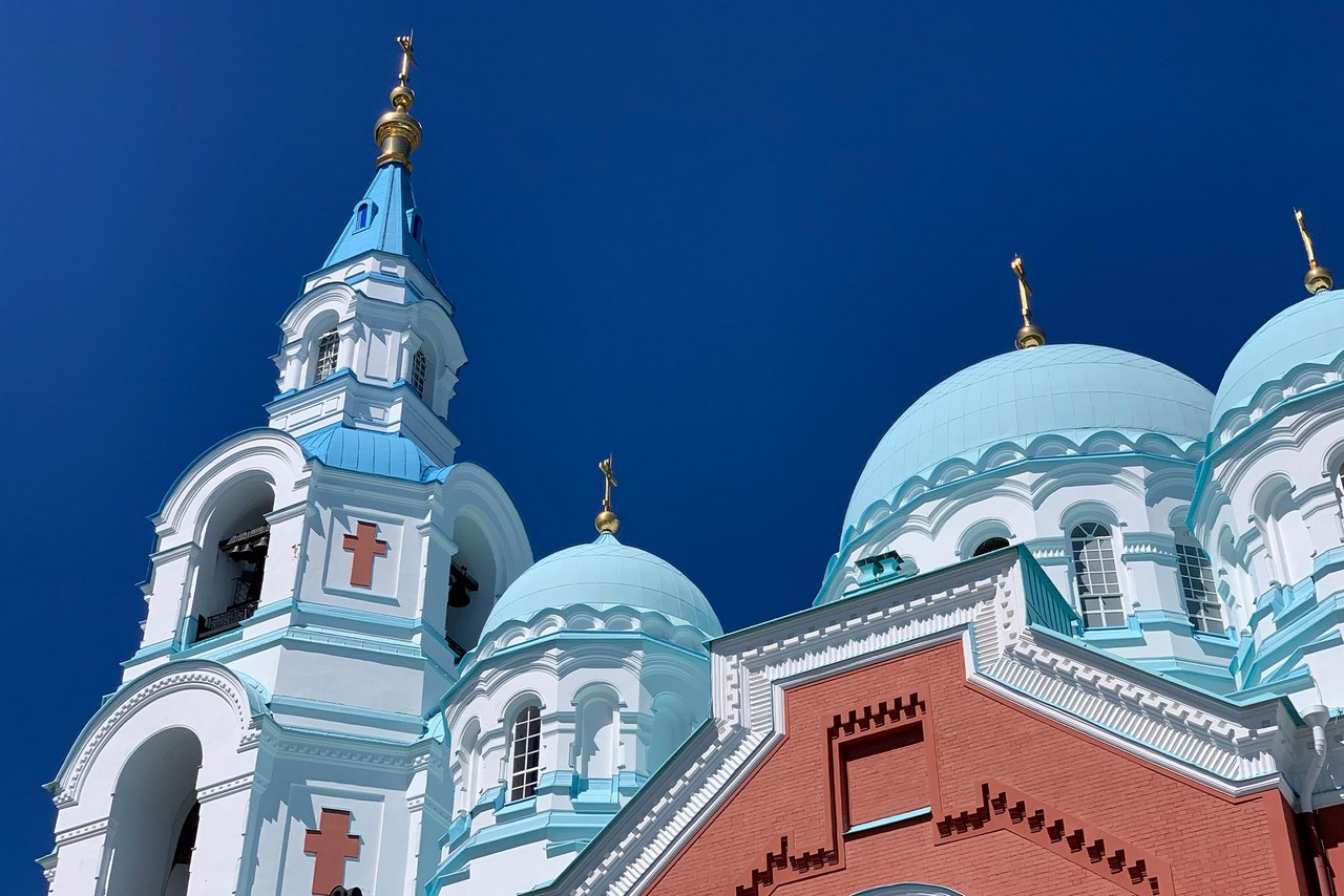 View of the top of Orthodox cathedral from the ground. Orthodox cathedral with the red base, white towers and blue domes topped with gilded crosses, bell tower decorated with red orthodox crossed