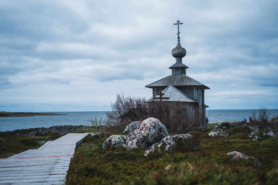 A small wooden chapel on the bank of a lake, wooden footpath, boulders