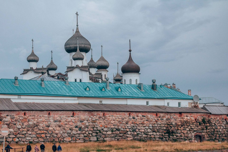 Ensemble of white orthodox churches with black onion domes behind the white monastery building with green roof, surrounded with stone fortress wall
