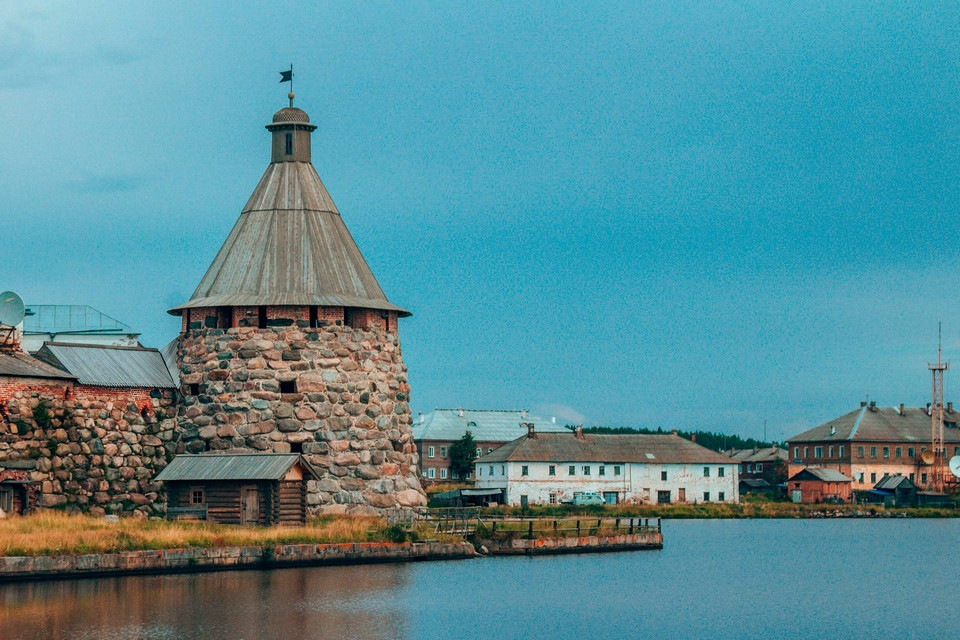 A stone tower of a fortress wall on the shore of a lake, old buildings in the background