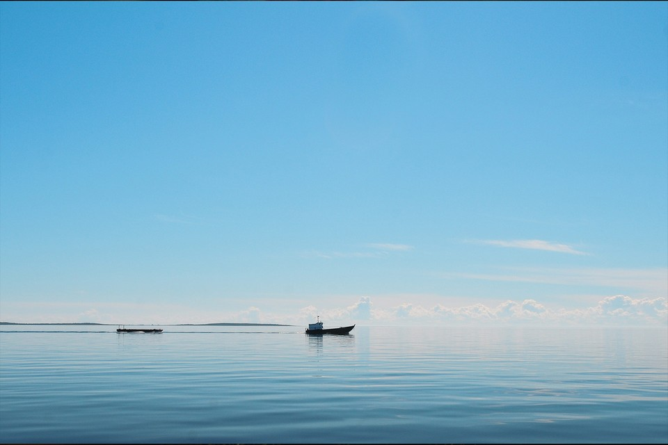 The sky blends with the sea, boat in the distance, blue sea and blue sky