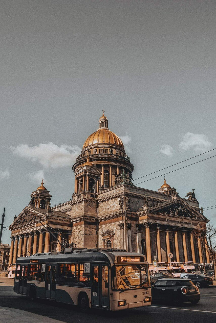 Large architectural landmark cathedral. The neoclassical exterior expresses the traditional Russian-Byzantine formula of a Greek-cross ground plan with a large central dome and four subsidiary domes, cathedral faced with gray and pink stone, it features many red granite columns with Corinthian capitals. A trolleybus in front of the cathedral.