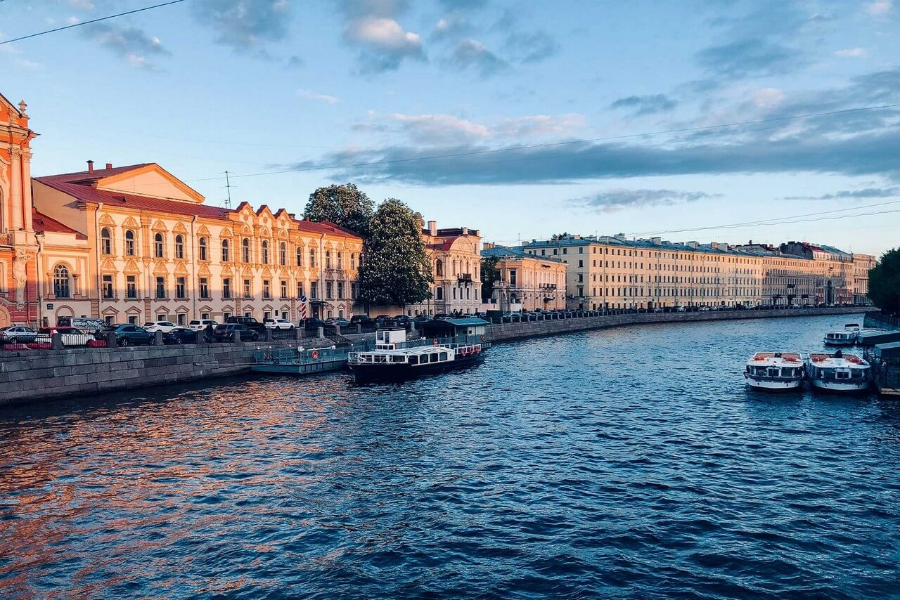 A river with granite embankments, canal and river cruise boats and a pier, beautiful old classic mansions on the embankment