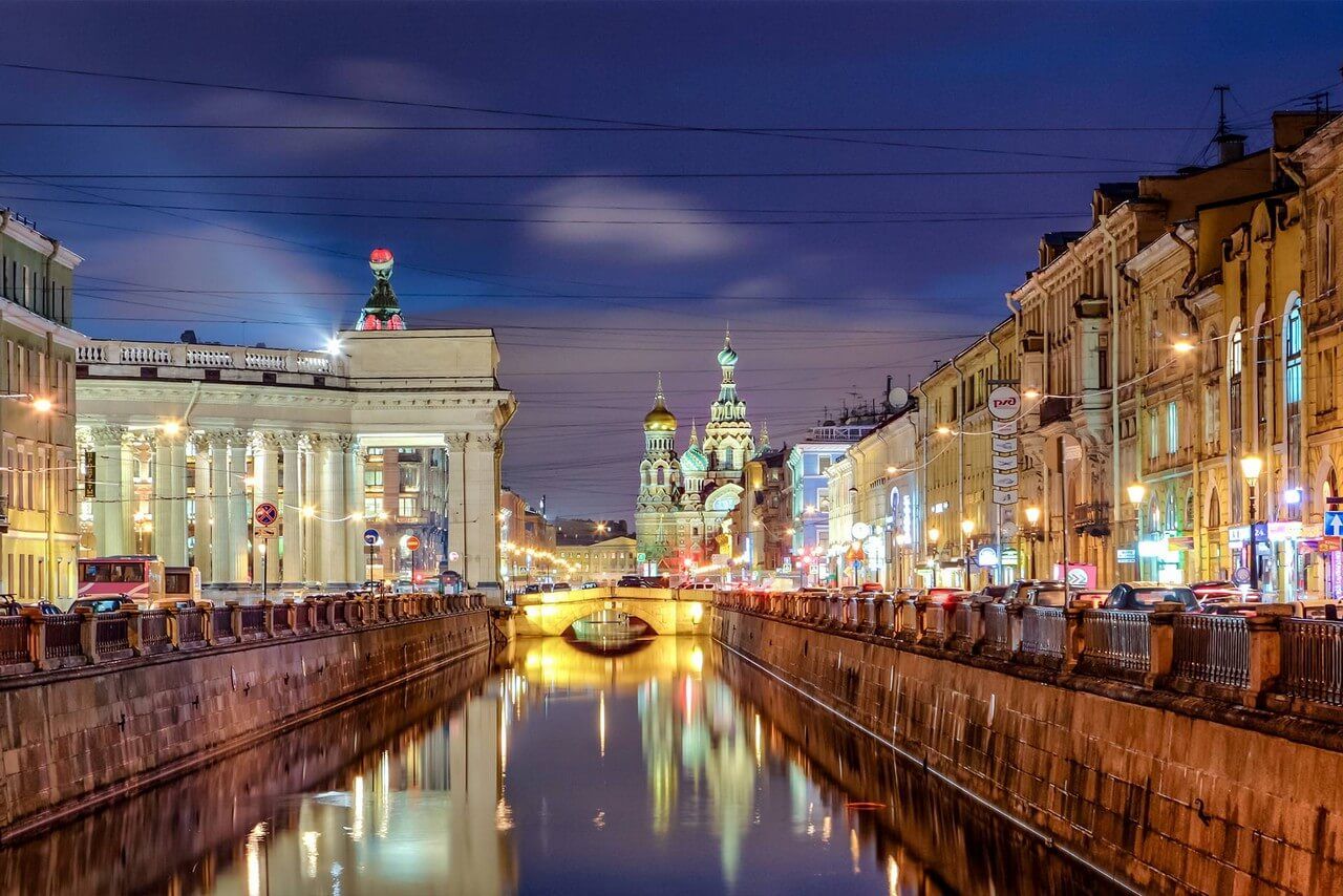 River with granite embankments. Bridge over the river illuminated at night, columns of a cathedral on the left, beautiful illuminated colorful cathedral from afar.