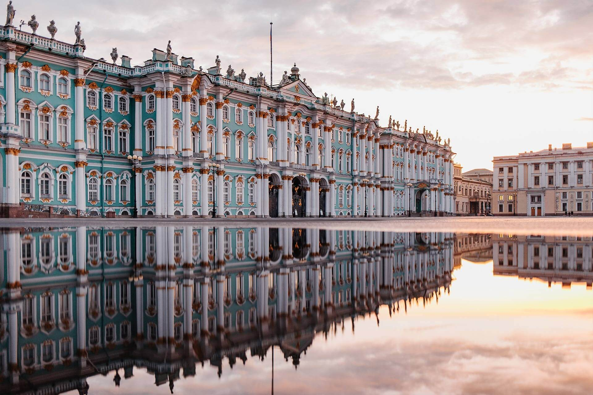Green and white palace in the Baroque style of mid-18th century Russian art. All the facades are embellished by a two-tier colonnade. Sculptures on the top of the palace, imperial residence. Reflection of the palace in a puddle of water.