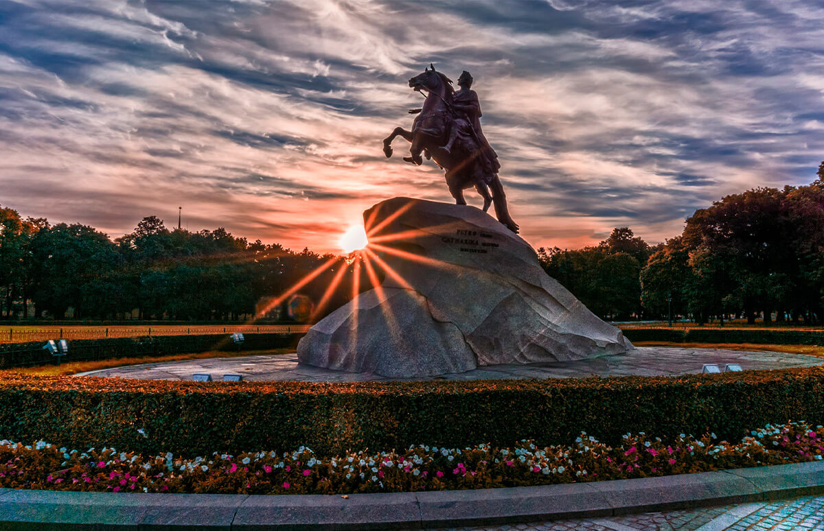 A statue of a man riding a horse. Horse stays on its hind legs on a giant stone. Sun shining brightly during the sunset. Beautiful clouds in Saint-Petersburg