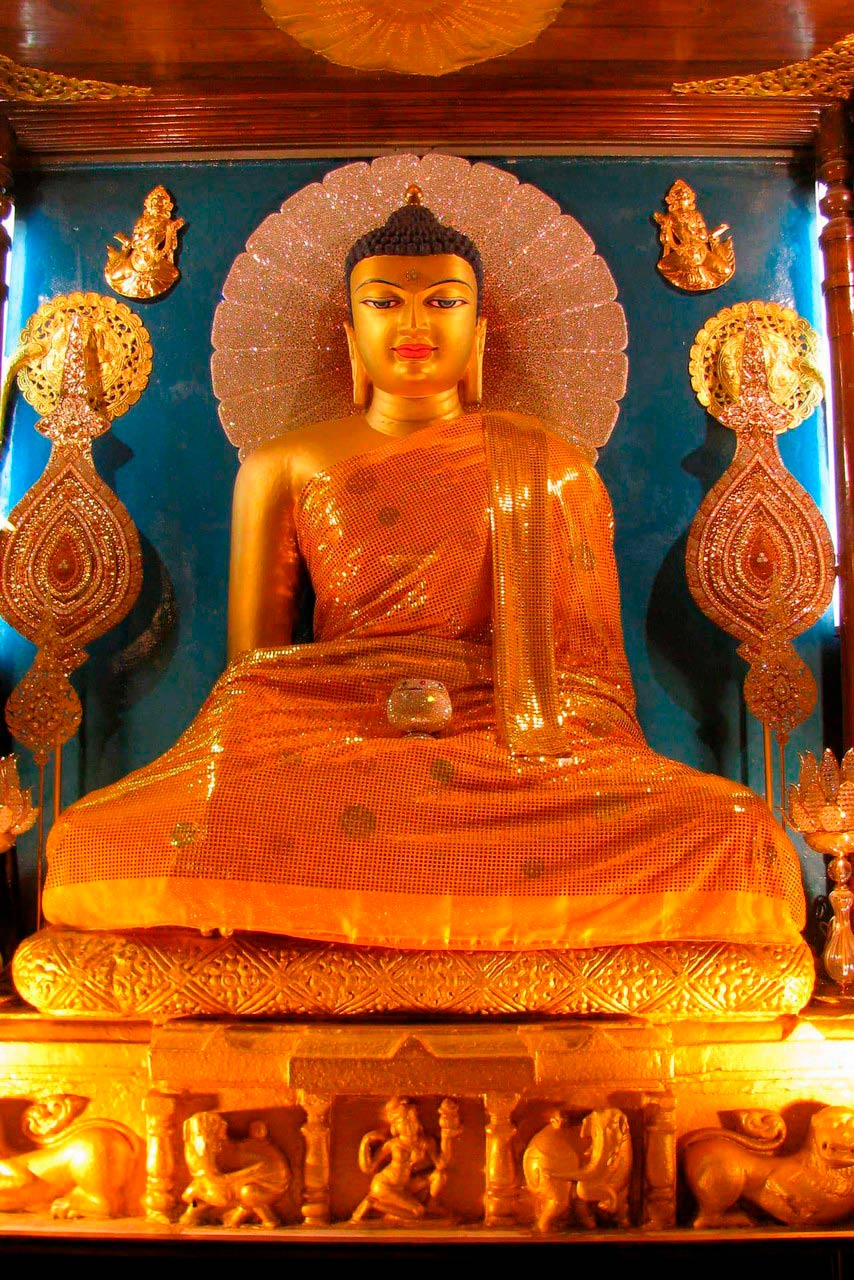A golden statue of sitting Buddha against the blue backdrop