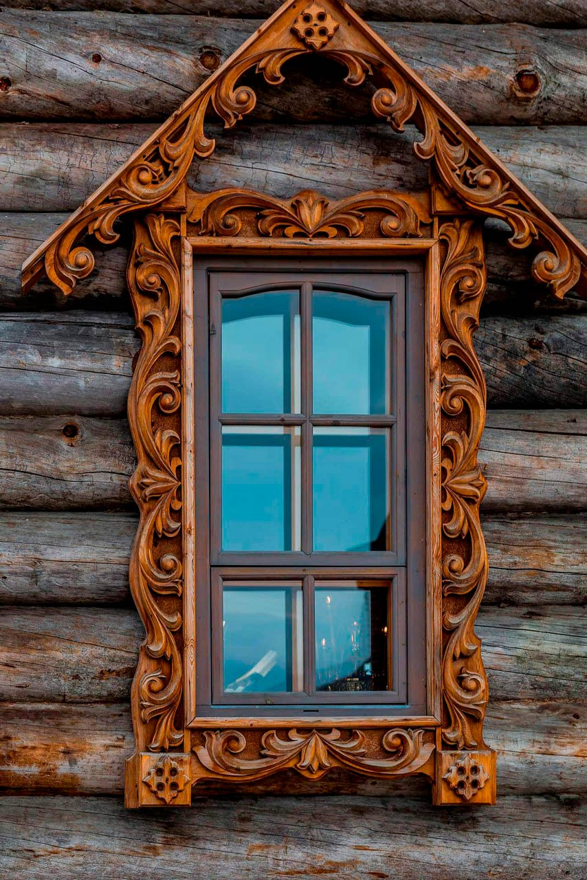 A carved wooden decorative window of a wooden house