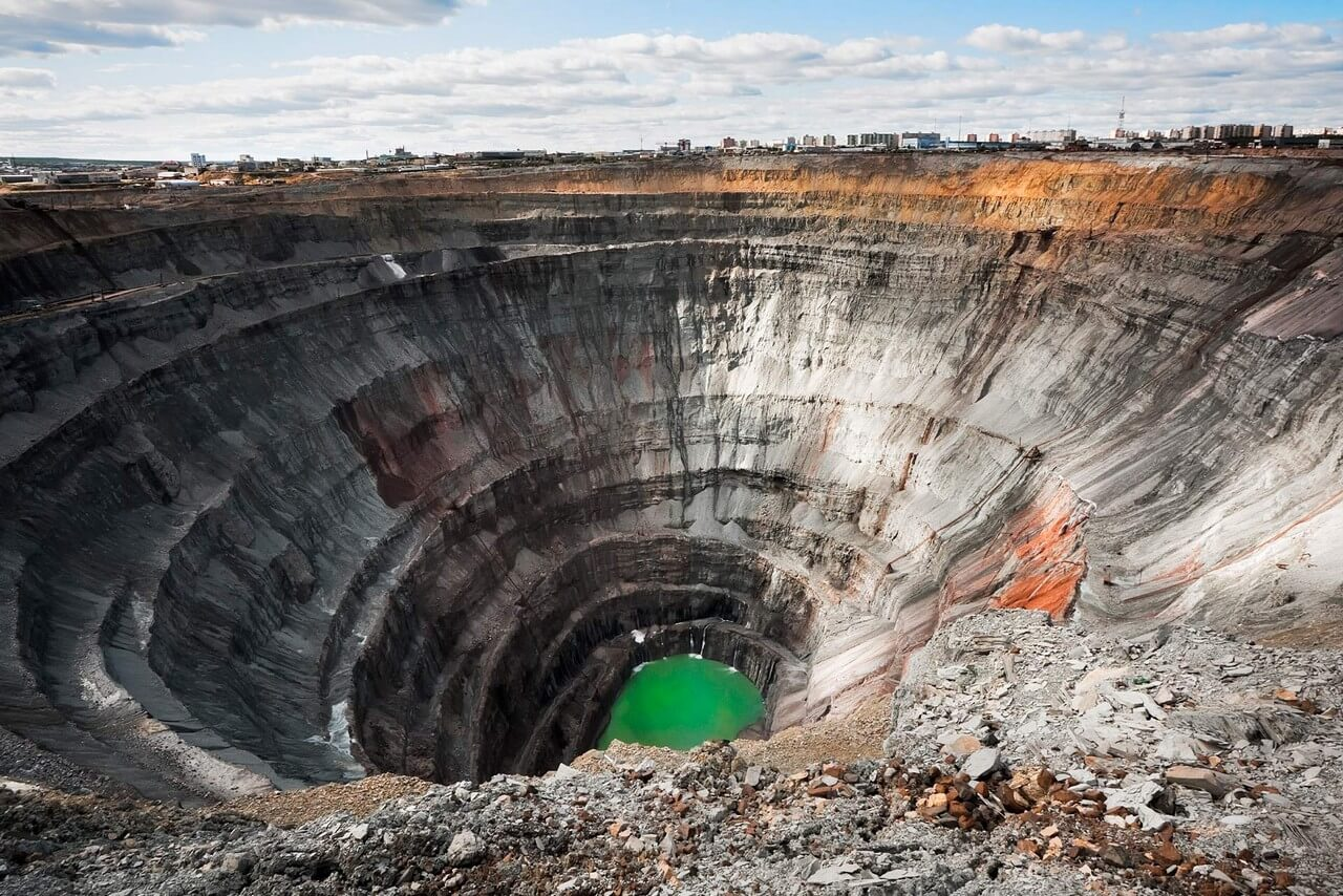 A giant pit with some water at the bottom of it