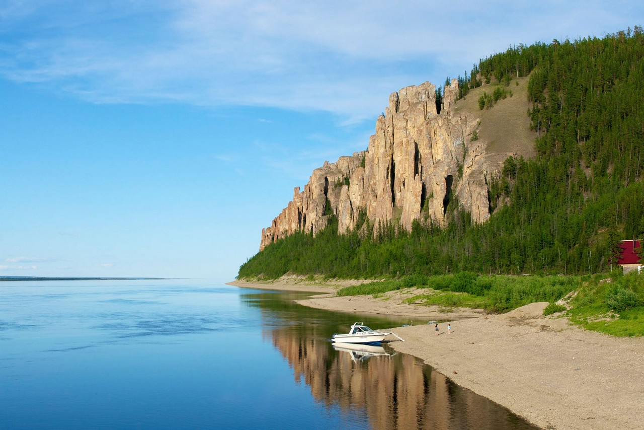 Rocks on the bank of the Lena river naturally formed in shape of pillars, small motorboat on the river