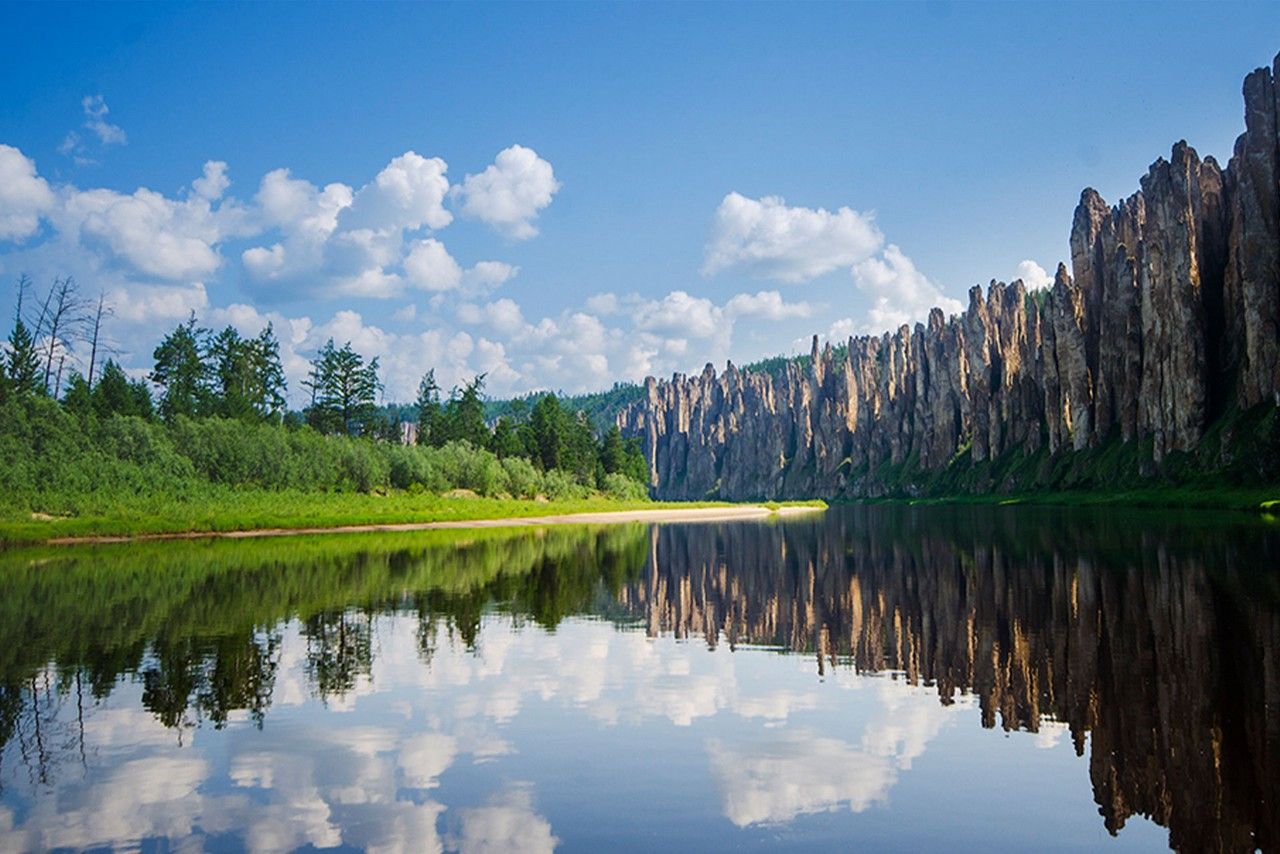 Rocks on the bank of the Lena river naturally formed in shape of pillars and a green forest and its reflection in the river