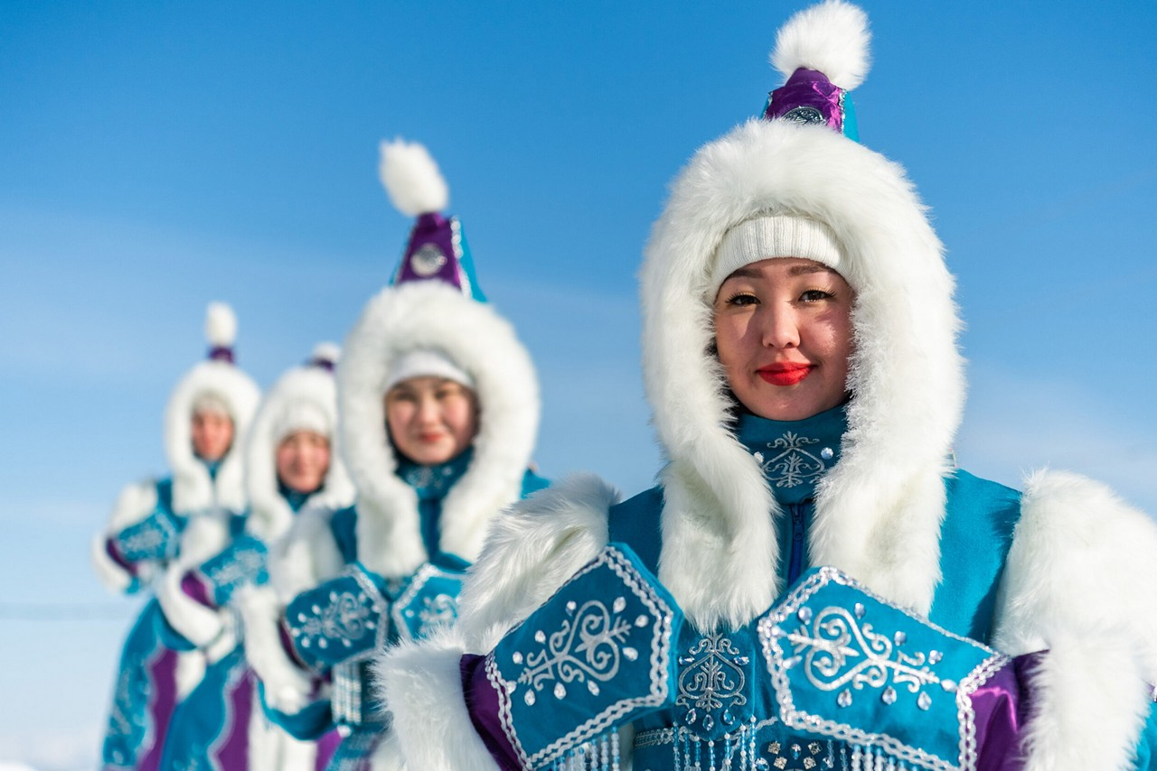 Indigenous women of Yakutia wearing blue winter coats with white decoration and white fur