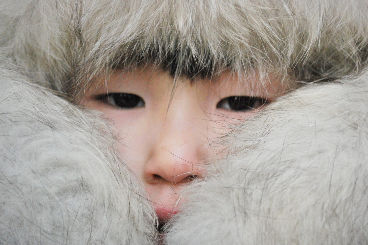 A Yakut child with half of his face covered with fur clothing