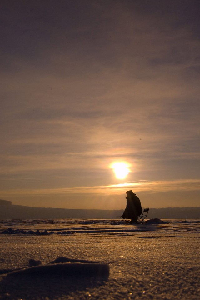 A fisherman sitting on a chair on a frozen lake or river waiting for a fish