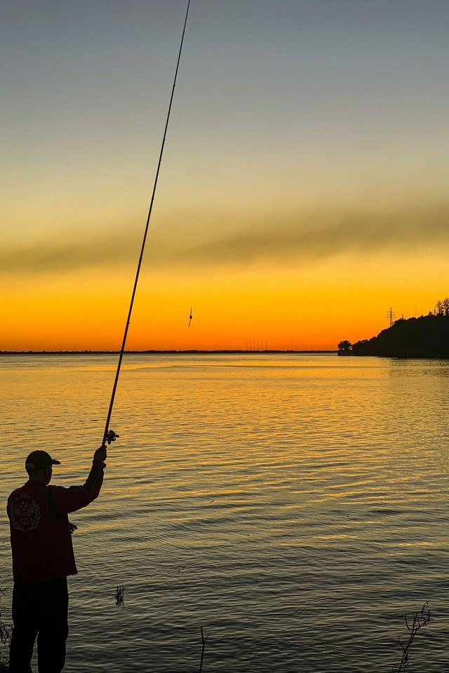A man with a fishing rod at sunset