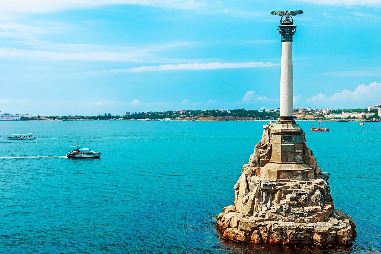 Monument in the middle of the sea consisting of a granite rock base, a column and an eagle on the top of it facing the sea