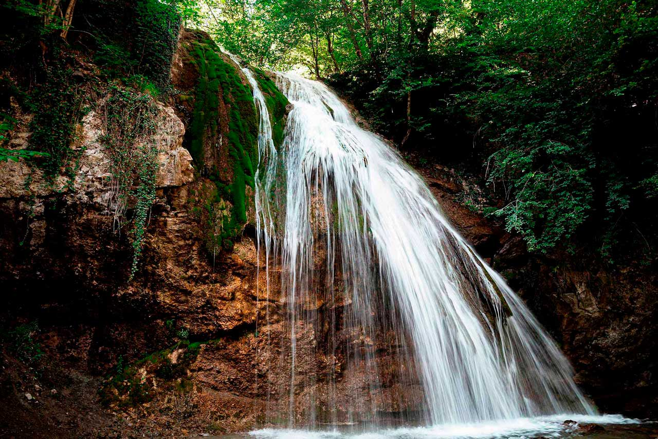 A waterfall in mountains surrounded with trees