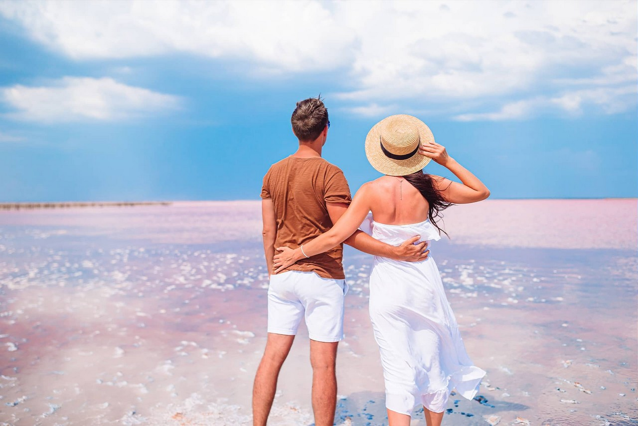 A couple wearing white clothes on the shore of a white lake. A woman is wearing a straw hat