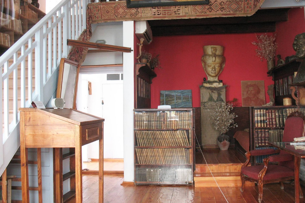 A room with a lot of books, ancient sculptures, a table and a staircase. Room is in red, white and brown colours.