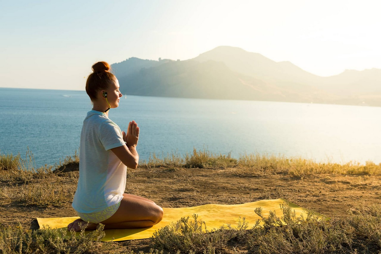 A girl sitting in yoga posture on the top of a hill and meditating with the sea view