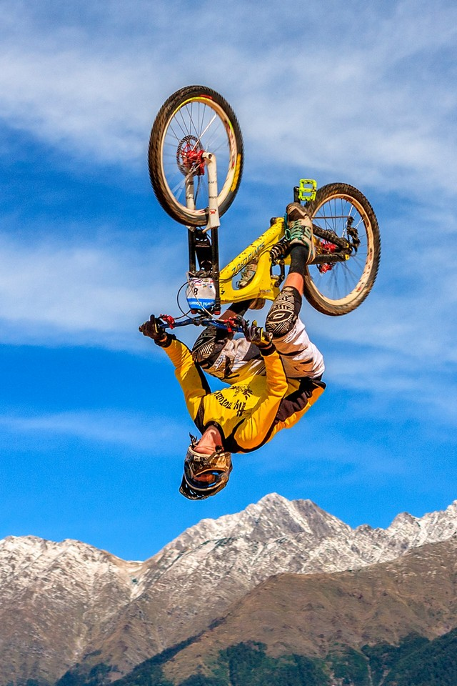 A man wearing yellow t-shirt doing a jump on his bike, a complex of tricks for downhill mountain biking from the height