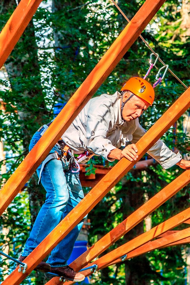 A man wearing a helmet and special equipment doing a high ropes course