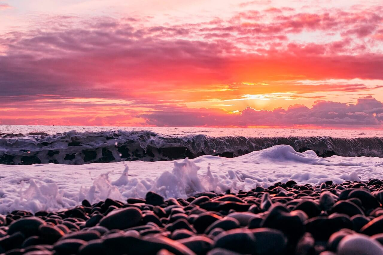 Beautiful sunrise, sea wave on pebble beach