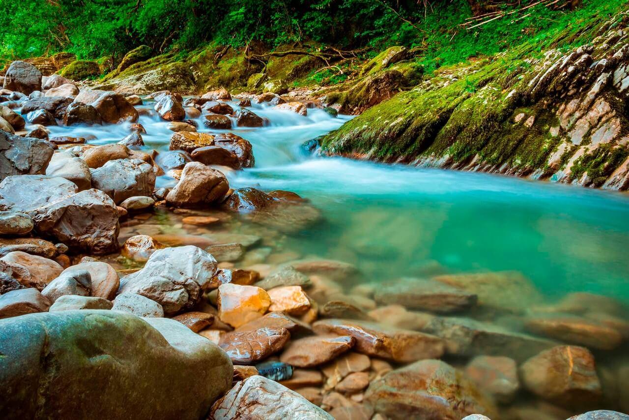 A transparent aquamarine mountain river, stones in the river