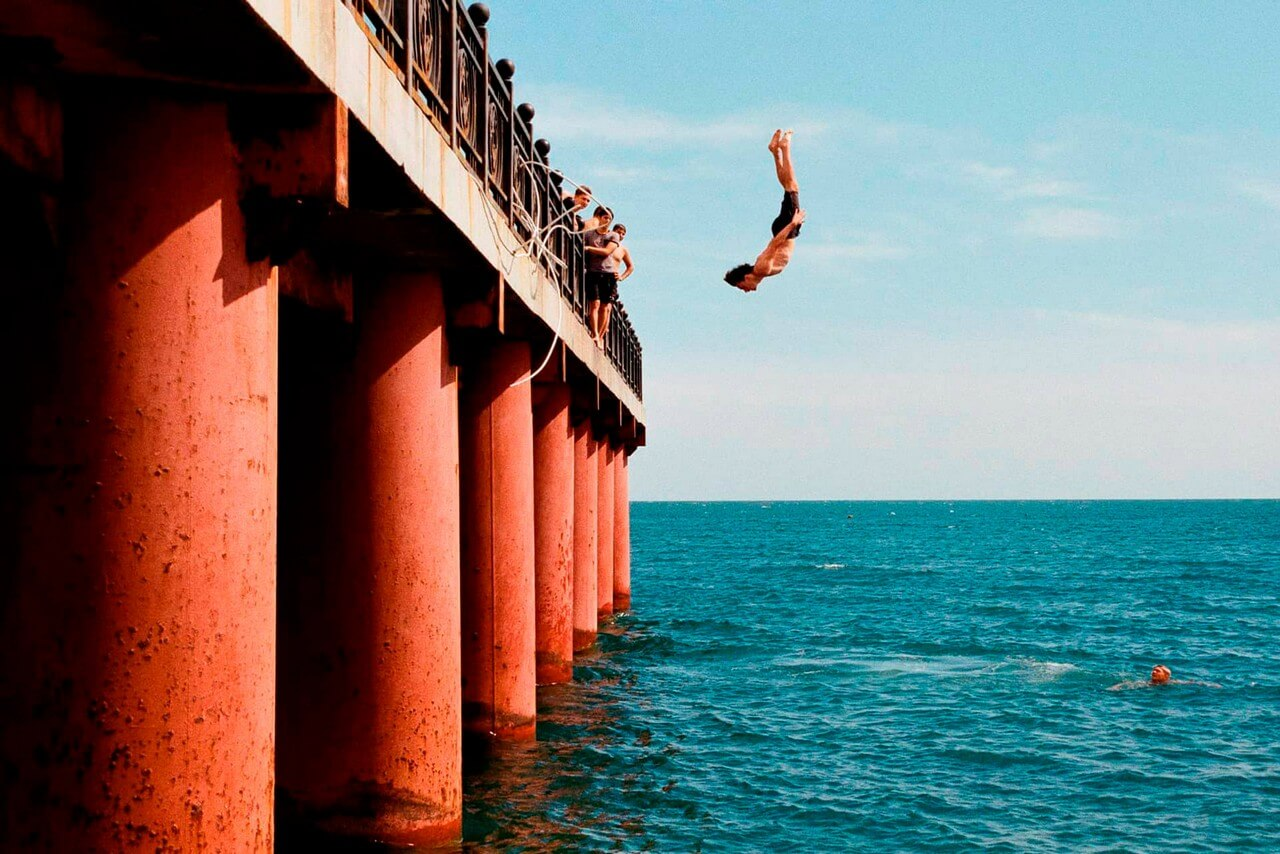 A man jumping of a high pier into the sea