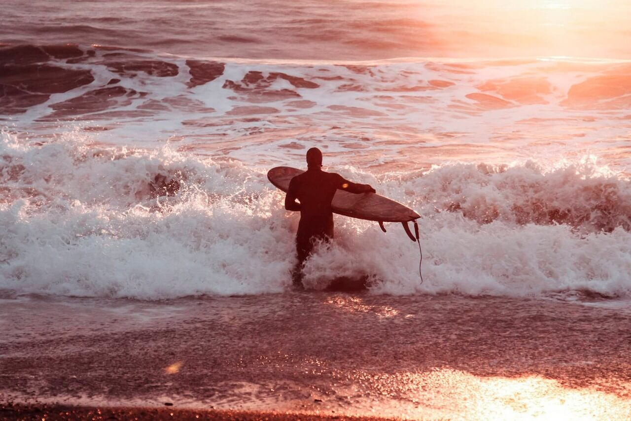 A man in a wetsuit going to surf, waves of the Black sea