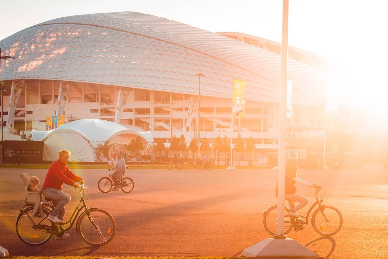 A stadium and people riding bikes in front of it in the sunshine