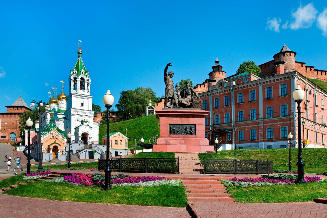 A small square with a monument of two men, one of them with a lifted hand, a little church on the left and a red building on the right, Kremlin wall behind